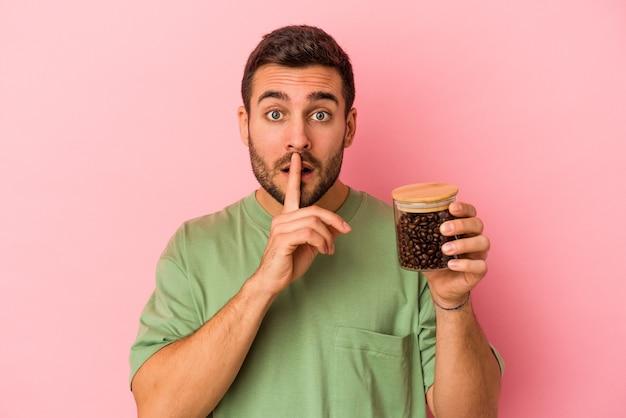 Młody kaukaski mężczyzna trzyma butelkę kawy na białym tle na różowej ścianie, zachowując tajemnicę lub prosząc o ciszę