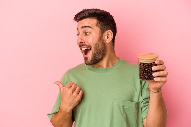 Młody kaukaski mężczyzna trzyma butelkę kawy na białym tle na różowych punktach ściany z kciukiem z dala, śmiejąc się i beztrosko