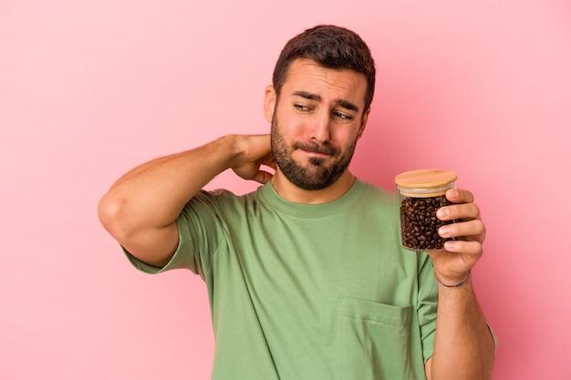 Młody kaukaski mężczyzna trzyma butelkę kawy na białym tle na różowym tle dotykając tyłu głowy, myśląc i dokonując wyboru.