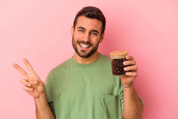 Młody kaukaski mężczyzna trzyma butelkę kawy na białym tle na różowym tle radosny i beztroski pokazując palcami symbol pokoju.