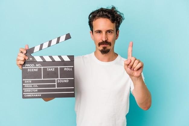Młody kaukaski mężczyzna trzyma clapperboard na białym tle na niebieskim tle pokazując numer jeden palcem.