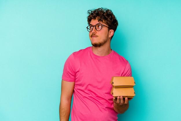 Młody kaukaski mężczyzna trzyma dwa hamburgery na białym tle na niebieskim tle, marząc o osiągnięciu celów i celów