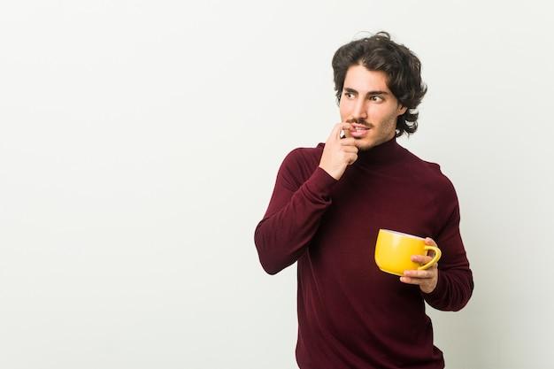 Młody kaukaski mężczyzna trzyma filiżankę kawy zrelaksowany, myśląc o czymś, patrząc na przestrzeń kopii.