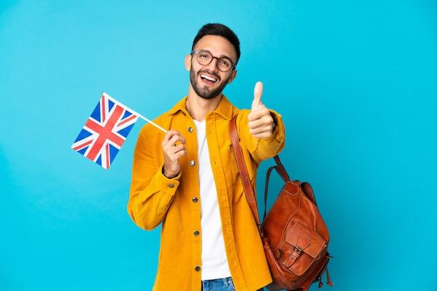 Młody kaukaski mężczyzna trzyma flagę zjednoczonego królestwa na białym tle na żółtej ścianie z kciukami do góry, ponieważ stało się coś dobrego