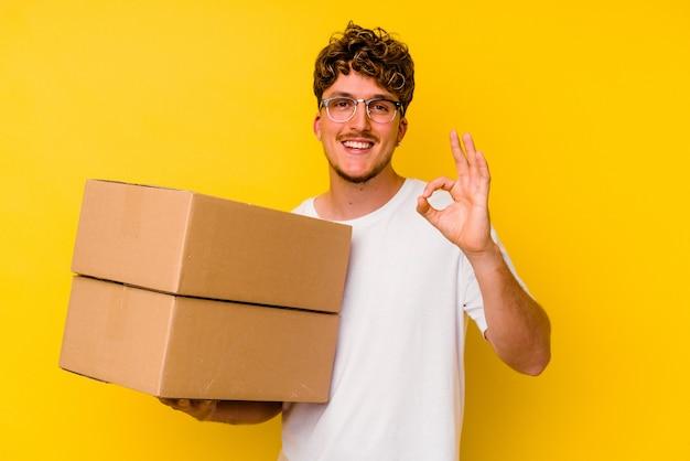Młody kaukaski mężczyzna trzyma karton na białym tle na żółtym tle wesoły i pewny siebie, pokazując ok gest.