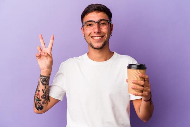 Młody kaukaski mężczyzna trzyma kawę na wynos na białym tle na fioletowym tle radosny i beztroski pokazując symbol pokoju palcami.