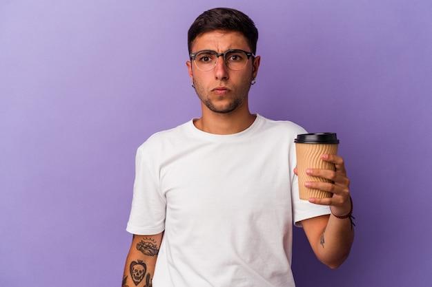 Młody kaukaski mężczyzna trzyma kawę na wynos na białym tle na fioletowym tle wzrusza ramionami i otwiera oczy zdezorientowany.