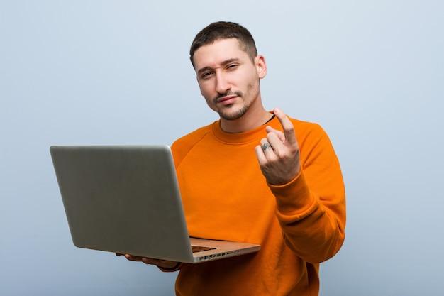 Młody kaukaski mężczyzna trzyma laptopa wskazując palcem na ciebie, jakby zapraszając podejść bliżej
