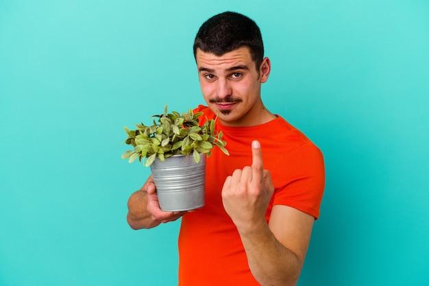 Młody kaukaski mężczyzna trzyma liść na białym tle na niebieskim tle, wskazując palcem na ciebie, jakby zapraszając, podejdź bliżej.