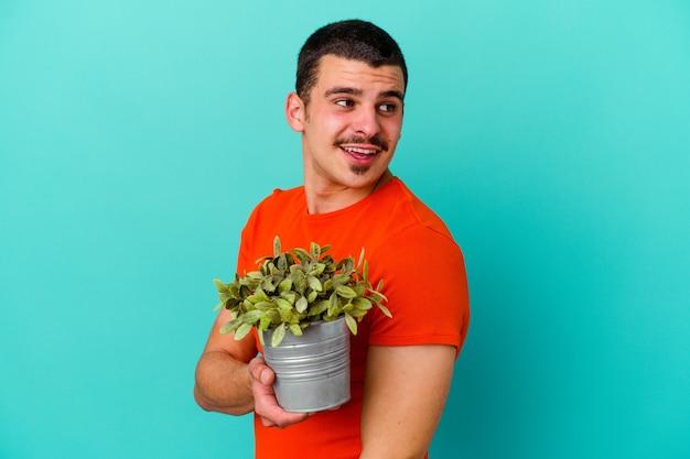 Młody kaukaski mężczyzna trzyma liść na białym tle na niebieskim tle wygląda na bok uśmiechnięty, wesoły i przyjemny.