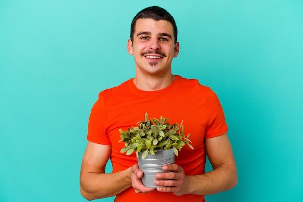 Młody kaukaski mężczyzna trzyma liść na białym tle na niebiesko szczęśliwy, uśmiechnięty i wesoły.