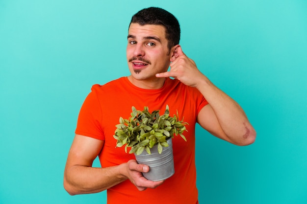 Młody kaukaski mężczyzna trzyma liść na niebiesko przedstawiający gest telefonu komórkowego palcami.