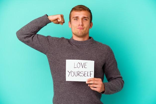 Młody kaukaski mężczyzna trzyma miłość siebie afisz na białym tle na niebieskiej ścianie