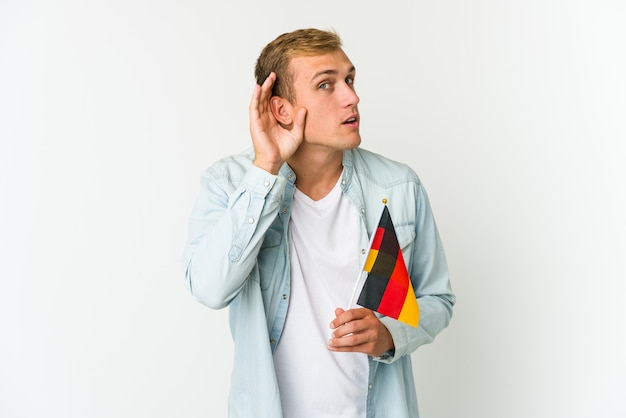 Młody kaukaski mężczyzna trzyma niemiecką flagę na białym tle osoba wskazując ręką na przestrzeni kopii koszuli, dumny i pewny siebie