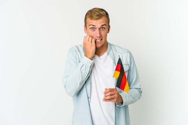 Młody kaukaski mężczyzna trzyma niemiecką flagę na białym tle zdezorientowany, czuje się niepewnie i niepewnie.