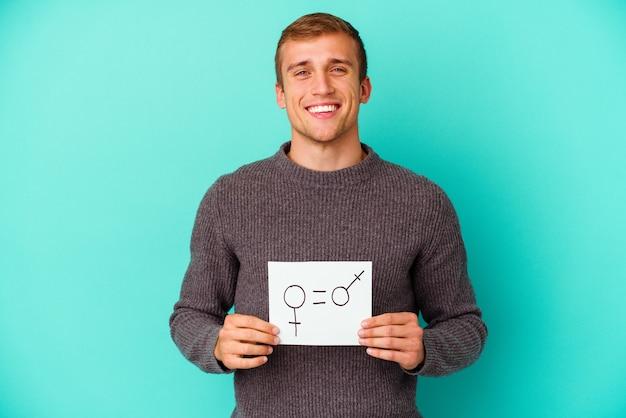 Młody kaukaski mężczyzna trzyma notatkę równości płci na białym tle na niebieskiej ścianie