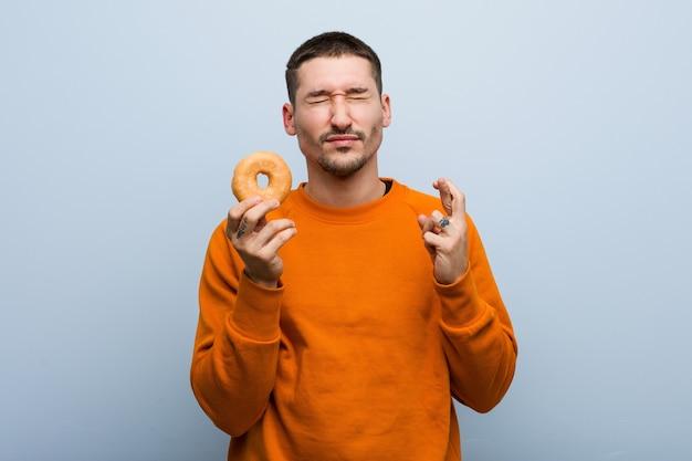 Młody kaukaski mężczyzna trzyma pączka trzymającego kciuki za szczęście