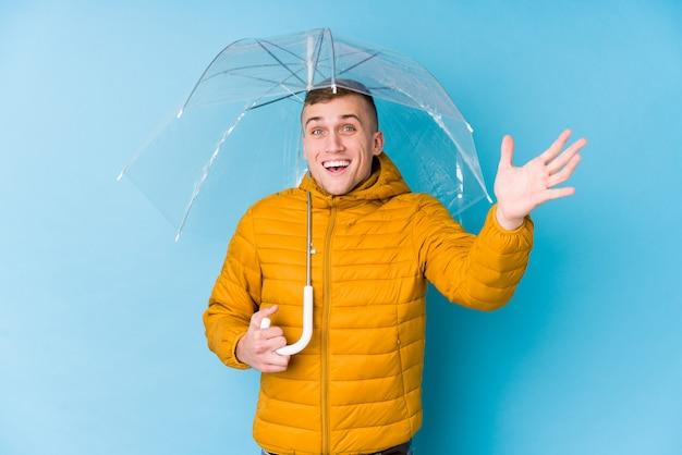 Młody kaukaski mężczyzna trzyma parasol otrzymujący miłą niespodziankę, podekscytowany i podnosząc ręce.