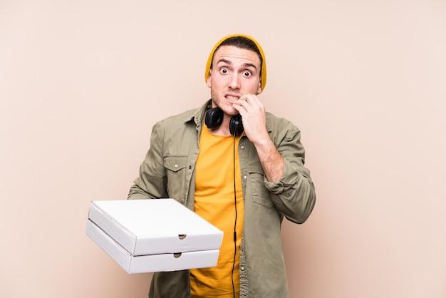 Młody kaukaski mężczyzna trzyma pizze gryząc paznokcie, nerwowy i bardzo niespokojny.