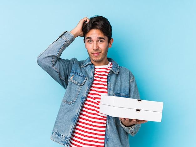 Młody kaukaski mężczyzna trzyma pizze na białym tle, będąc zszokowanym, przypomniała sobie ważne spotkanie.