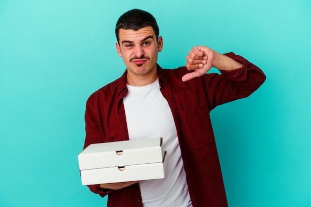 Młody kaukaski mężczyzna trzyma pizze na białym tle na niebieskim tle pokazując gest niechęci, kciuk w dół. koncepcja niezgody.