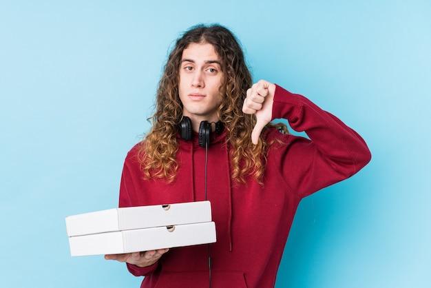 Młody kaukaski mężczyzna trzyma pizze na białym tle, pokazując gest niechęci, kciuk w dół. pojęcie sporu.