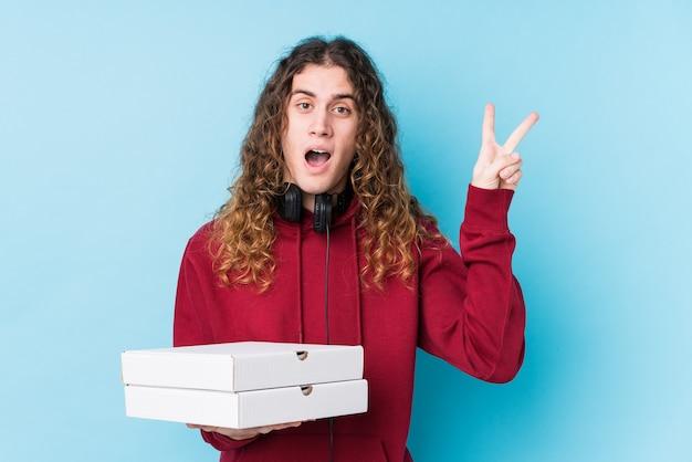 Młody kaukaski mężczyzna trzyma pizze na białym tle radosny i beztroski, pokazując palcami symbol pokoju.