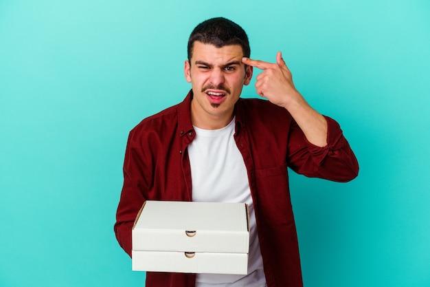 Młody kaukaski mężczyzna trzyma pizze na niebiesko, pokazując gest rozczarowania palcem wskazującym.