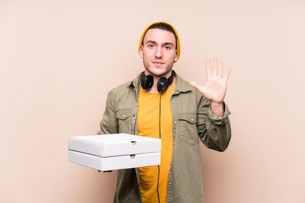 Młody kaukaski mężczyzna trzyma pizze uśmiechnięty wesoły pokazując numer pięć palcami.