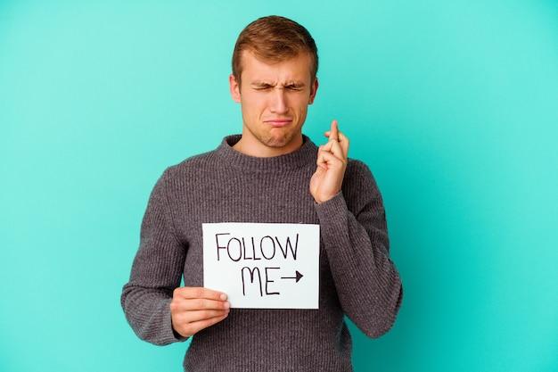 Młody kaukaski mężczyzna trzyma plakietkę follow me na białym tle na niebieskiej ścianie, skrzyżowanymi palcami za szczęście