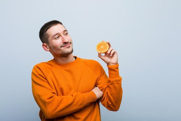 Młody kaukaski mężczyzna trzyma pomarańczowy uśmiechnięty pewnie ze skrzyżowanymi rękami.