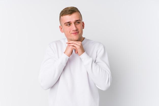 Młody kaukaski mężczyzna trzyma ręce pod brodą, radośnie patrzy na bok.