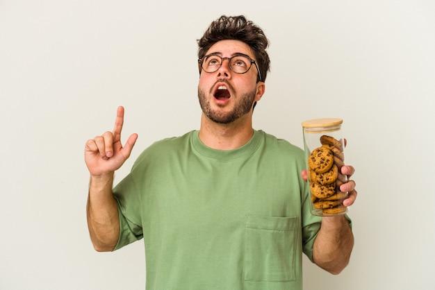Młody kaukaski mężczyzna trzyma słoik ciasteczka na białym tle wskazując na górę z otwartymi ustami.