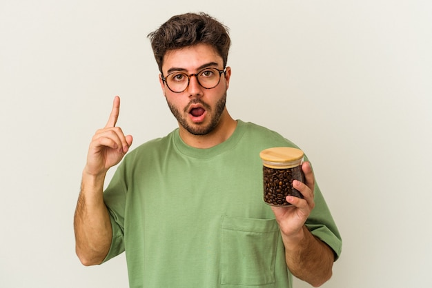 Młody kaukaski mężczyzna trzyma słoik kawy na białym tle o jakiś świetny pomysł, pojęcie kreatywności.