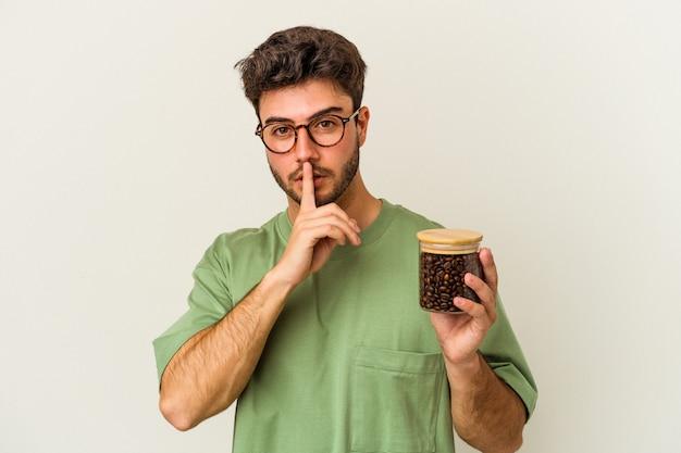 Młody kaukaski mężczyzna trzyma słoik kawy na białym tle, zachowując tajemnicę lub prosząc o ciszę.
