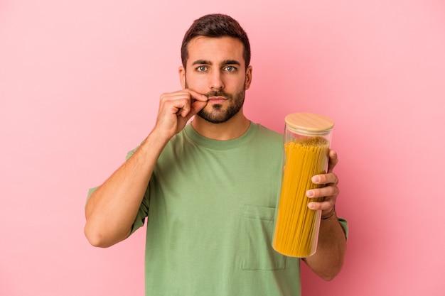 Młody kaukaski mężczyzna trzyma słoik makaronu na białym tle na różowym tle z palcami na ustach zachowując tajemnicę.