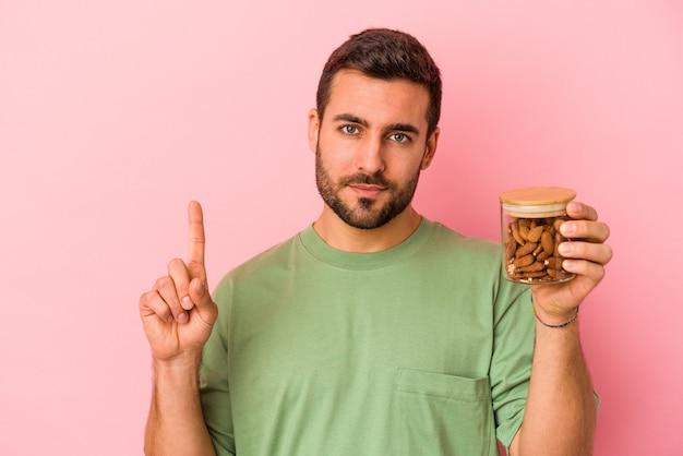 Młody kaukaski mężczyzna trzyma słoik migdałów na białym tle na różowym tle pokazuje numer jeden z palcem.