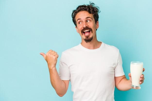 Młody kaukaski mężczyzna trzyma szklankę mleka na białym tle na niebieskim tle wskazuje palcem kciuka, śmiejąc się i beztrosko.