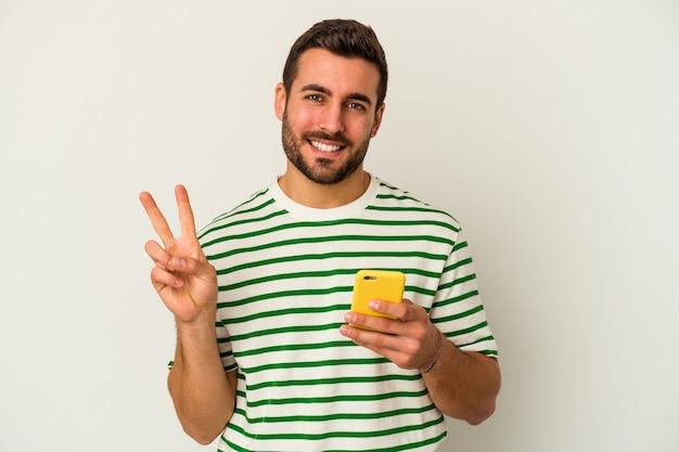Młody kaukaski mężczyzna trzyma telefon komórkowy na białym tle na białym tle pokazuje numer dwa palcami.