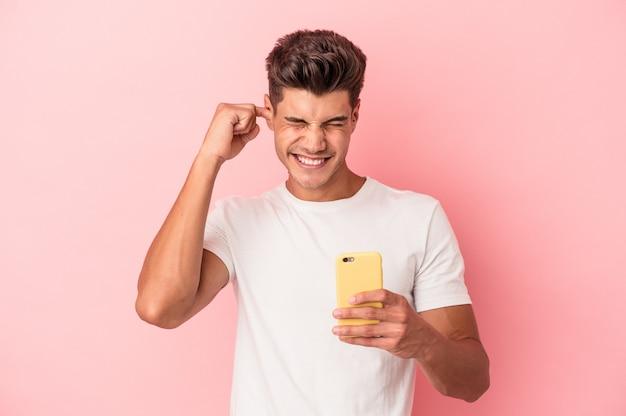 Młody kaukaski mężczyzna trzyma telefon komórkowy na białym tle na różowym tle zakrywając uszy rękami.