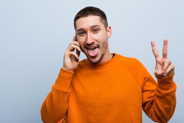 Młody kaukaski mężczyzna trzyma telefon pokazuje numer dwa palcami.