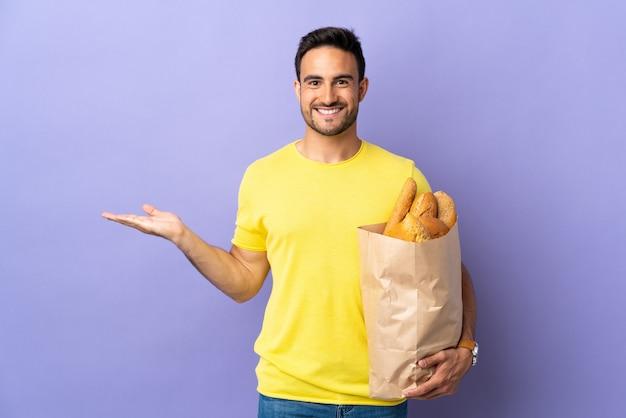 Młody kaukaski mężczyzna trzyma torbę pełną pieczywa na białym tle na fioletowym tle wyciągając ręce na bok za zaproszenie