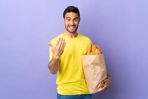 Młody kaukaski mężczyzna trzyma torbę pełną pieczywa na białym tle na fioletowym zapraszając do przyjazdu