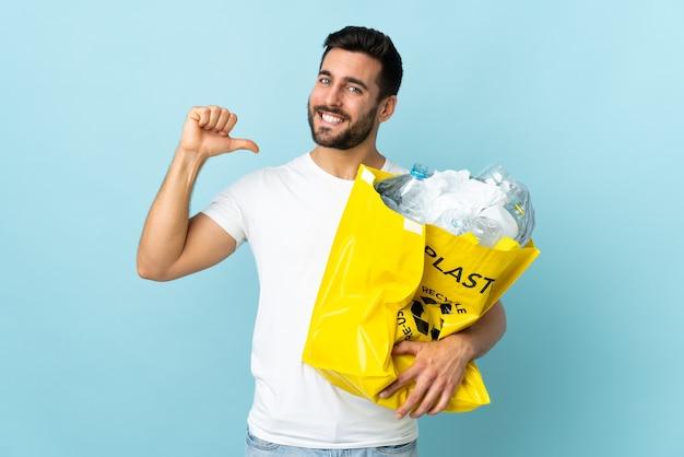 Młody kaukaski mężczyzna trzyma torbę pełną plastikowych butelek do recyklingu na białym tle na niebieskiej ścianie dumny i zadowolony z siebie