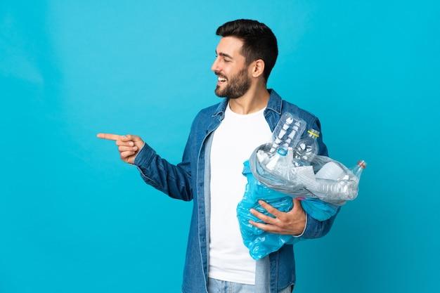 Młody kaukaski mężczyzna trzyma torbę pełną plastikowych butelek do recyklingu na białym tle na niebieskim tle, wskazując na bok, aby przedstawić produkt