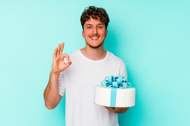 Młody kaukaski mężczyzna trzyma tort na białym tle na niebieskim tle wesoły i pewny siebie, pokazując ok gest.