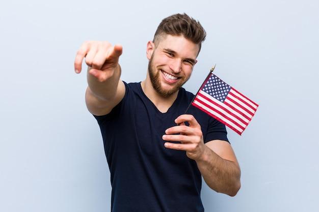 Młody kaukaski mężczyzna trzyma wesołej flagi stanów zjednoczonych uśmiecha się do przodu.