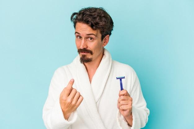 Młody kaukaski mężczyzna trzyma żyletkę na białym tle na niebieskim tle, wskazując palcem na ciebie, jakby zapraszając się bliżej.