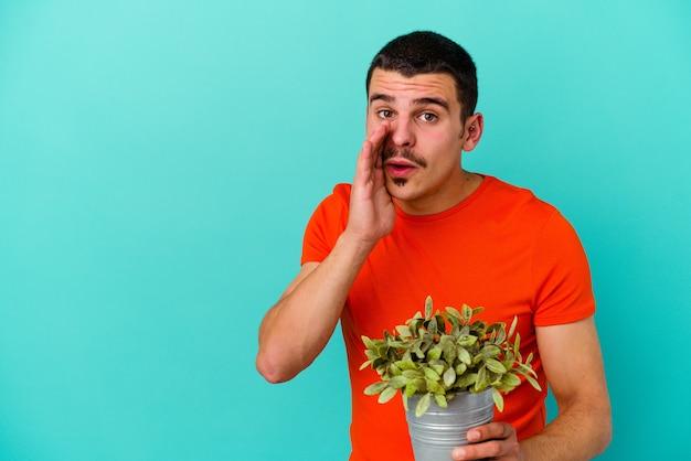 Młody kaukaski mężczyzna trzymający liść na białym tle na niebieskim tle mówi tajne gorące wiadomości o hamowaniu i odwraca wzrok