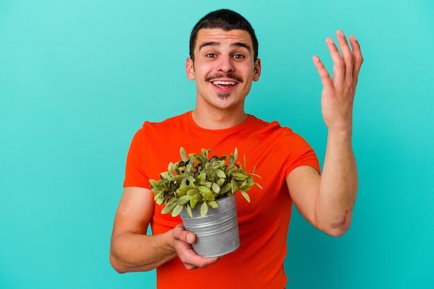 Młody kaukaski mężczyzna trzymający liść na niebieskim tle odbiera miłą niespodziankę, podekscytowany i podnosząc ręce.
